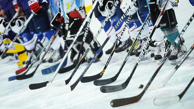 Хоккеисты с клюшками на льду