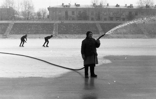 """«Заливка льда на стадионе """"Металлург""""», Новокузнецк, 11 февраля 1984 года. Участники ТРИВА не расставались с камерами и за пределами завода и рабочего дня. В результате большая часть работ — это повседневные сценки на улицах Новокузнецка 80-х годов. Принципы, по которым снимали фотографы ТРИВА, — отказ от ретуши и кадрирования отснятого материала. Но главное — полный отказ от постановочных кадров. Все, что происходит в кадре, происходит на самом деле; человек с камерой никогда не подсказывает героям, как делать это фотогеничнее, и не просит повторить упущенный им момент."""