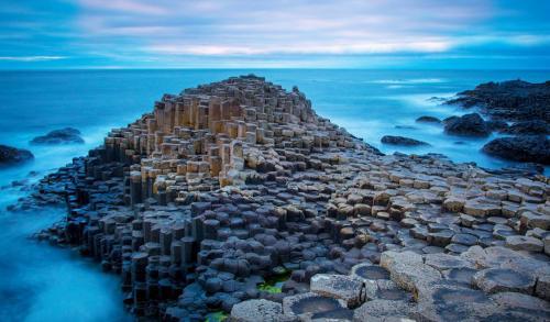 Causeway Coastal Route Северная Ирландия Тысячи шестиугольных базальтовых колонн считаются мостовой троллей, прошедших здесь от гнева Одина и других богов. На самом же деле, эти причудливые скальные образования — результат извержения вулкана.