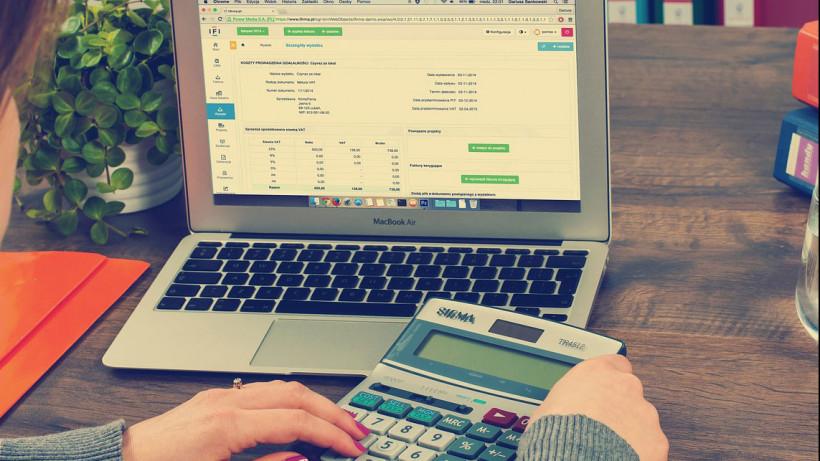 Девушка за компьютером с калькулятором проверяет расчеты