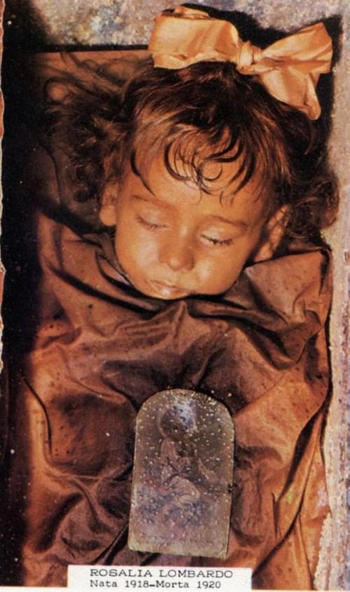 3. Двухлетняя Розалия Ломбардо Катакомбы капуцинов в итальянском Палермо — это жуткое место, некрополь, привлекающий туристов со всего света множеством мумифицированных тел разной степени сохранности. Но символ этого места — это детское личико Розалии Ломбардо, двухлетней девочки, умершей от пневмонии в 1920 году. Ее отец, будучи неспособным справиться с горем, обратился к известному медику Альфредо Салафии с просьбой сохранить тело дочери. Теперь оно заставляет шевелиться волосы на голове у всех без исключения посетителей подземелий Палермо — потрясающим образом сохранившееся, умиротворенное и настолько живое, что кажется, будто Розалия лишь ненадолго задремала, оно производит неизгладимое впечатление.