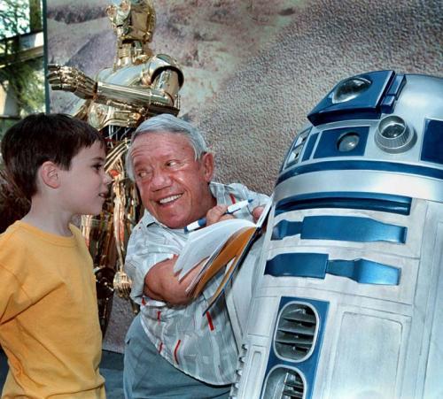 """Для Кенни Бейкера автографы – редкое удовольствие Актер и комик Кенни Бейкер совершил действительно звездный взлет, снявшись в роли робота R2-D2 в фильмах франшизы «Звёздные войны». Его друг по сценарию C-3PO также стал невероятно популярен, хотя актера Энтони Дэниелса на улицах также не узнавали. Интересно, что на самом деле отношения у кинематографических роботов за пределами площадки не складывались. Это не помешало им, однако, сняться в семи лентах. На самом деле, эти роли были для актеров тяжелым испытанием: костюмы были достаточно сложными «в управлении», а съемки в Тунисе в жару превращались в настоящую пытку. Кенни вспоминал об этом: «Я не мог самостоятельно выбраться из робота, и когда говорили: «Снято, прервемся на ланч», случалось, что меня забывали вытащить». А Энтони- C-3PO даже получил на площадке травму: «Первое облачение в костюм закончилось настоящим ЧП. Я сделал два шага, и вдруг левая нога пластикового костюма лопнула под давлением моей. Осколки пластика впились в мягкие ткани. И мы сняли пластиковую ногу. Я играл в одной """"ноге"""". Вот тогда-то меня и начала охватывать паника: на что же я подписался?»"""