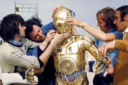 Энтони Дэниелс облачается в костюм C-3PO А для воплощения инопланетянина Чубакки проблема была противоположной – требовался гигант. Поэтому непрофессиональный актер Питер Мехью получил эту роль без проб, он просто встал с кресла, и был тут же утвержден – не часто на улицах встретить человека ростом в 221 см. Бывшего фельдшера облачили в костюм, связанный из шерсти ангорских коз, и также отправили на съемки в жаркие страны. Когда его спрашивали, каково это было, тот сравнивал свое состояние с едой в микроволновке. Кстати, голос, которым разговаривает Чубакка – это смесь криков различных животных: медведя, льва, тигра и моржа.