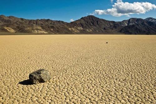 Движущиеся камни в Долине Смерти Это естественное природное явление наблюдается в Рейстрак Плая, Национальном парке Долины Смерти, Калифорния. Горный ландшафт там чередуется с аллювиальными долинами, в то время как Рейстрак Плая — одно из самых живописных и мистических сухих озер. Так его назвали из-за многочисленных движущихся камней. Вы можете фактически ясно отличить их следы на поверхности пустыни. Поездки этих «Парусных Камней» являются большой геологической тайной и явлением, которое, как полагают, создано серьезными ветрами, скоростью камней, тонким слоем песка и многими другими факторами. Побывать в Рейстрак Плая — настоящее везение, где Вы будете окружены драматическими горными вершинами, над которыми доминируют только бесформенные белые облака.