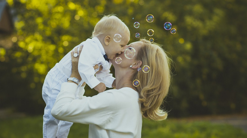 Мама с ребенком на руках в парке