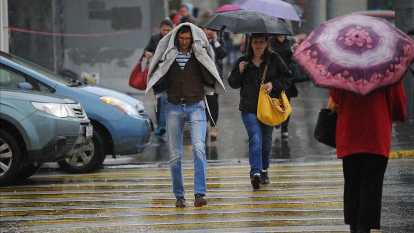 Люди идут по пешеходному переходу во время дождя
