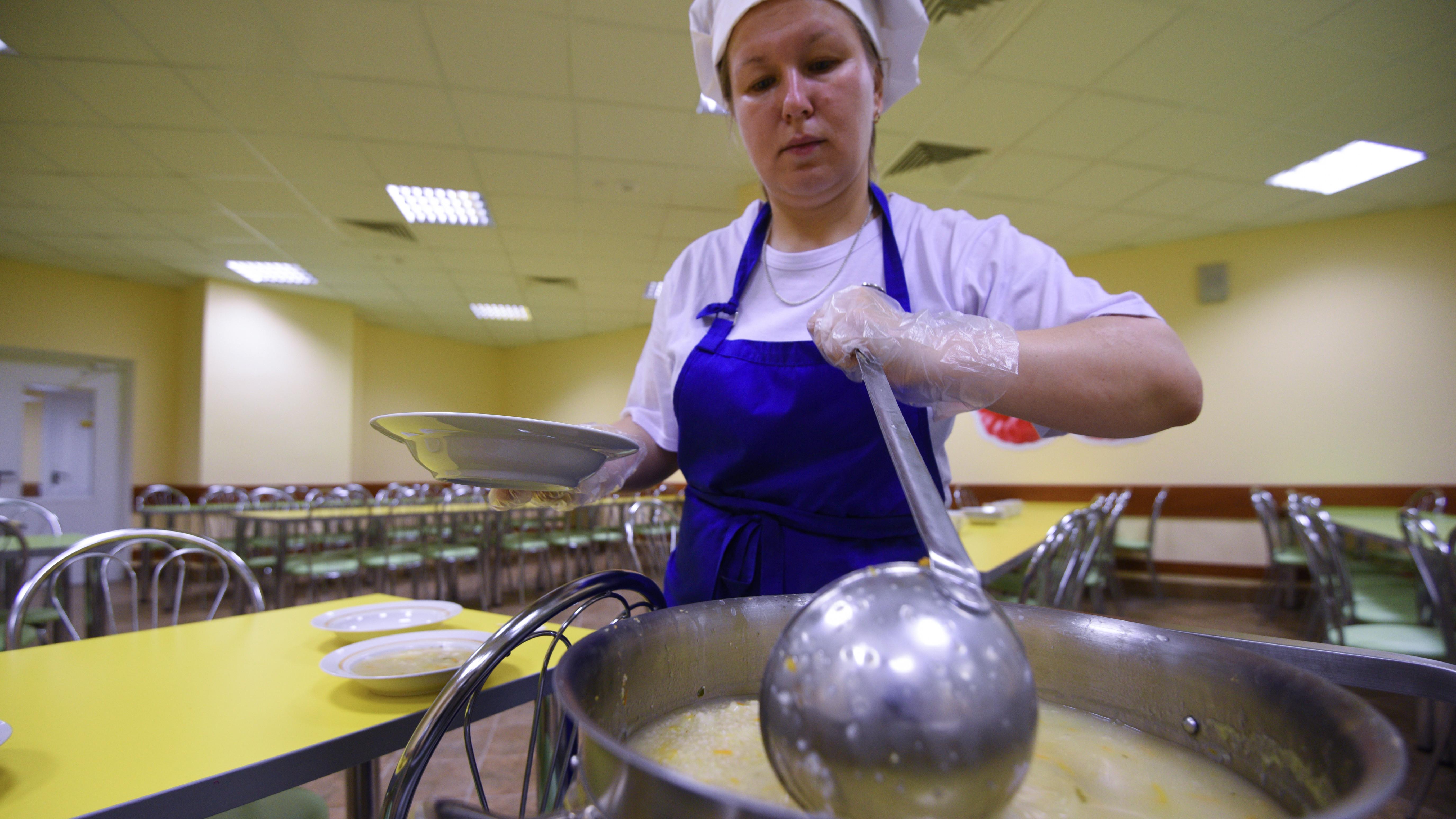 Повар раскладывает еду по тарелкам в школьной столовой
