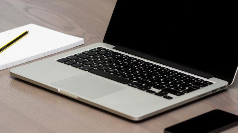 Ноутбук, блокнот, карандаш и смартфон на столе