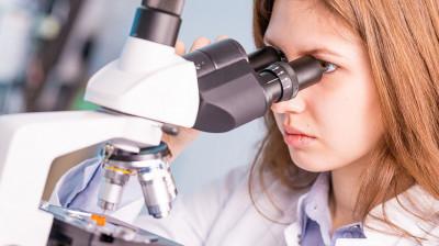 Научный работник смотрит в микроскоп
