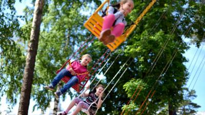 Дети катаются на карусели в летнем парке