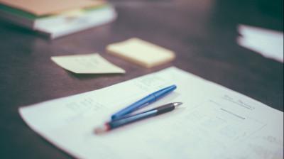 Бумаги, ручки и стикеры на столе